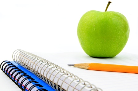 Close up of a pencil and apple resting on a blank lined notebook photo