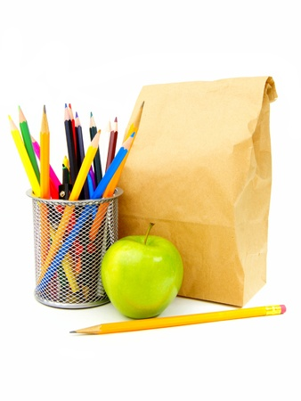pencil holder: School lunch bag with apple, pencil and school supplies over white