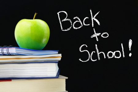 back up: Back to School written on a blackboard with books and apple in front