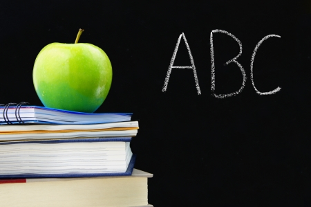 ABC written on a blackboard with books and apple in front