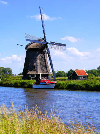Traditional Dutch windmill along a canal near Alkmaar, Netherlands photo