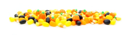 Long edge or border of assorted Halloween candy over white photo