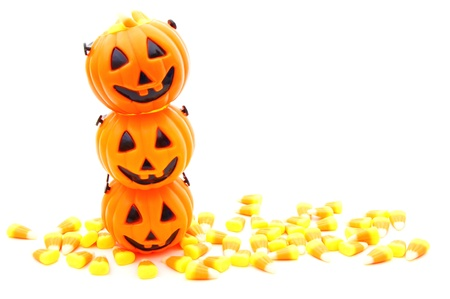Stacked Halloween jack-o-lantern candy holders with candy corn over white photo