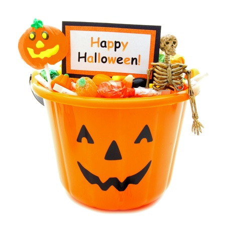 Halloween candy holder full of candy with Happy Halloween tag over white photo