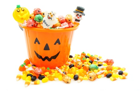 Jack-o-lantern candy pail with a pile of colorful Halloween candy photo