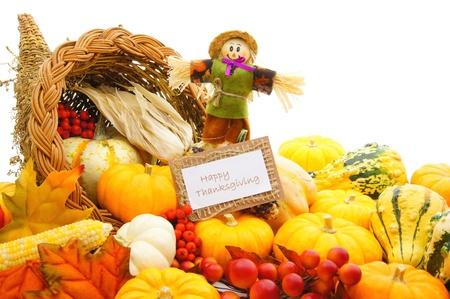 cuerno de la abundancia: Feliz tarjeta de Acción de Gracias y espantapájaros entre un cuerno de la abundancia de verduras de otoño