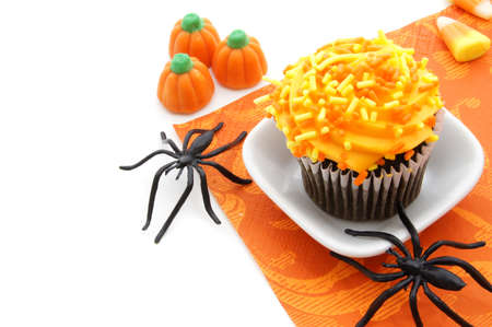 Halloween cupcake and candy with spiders over white photo