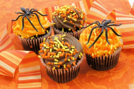 Halloween cupcake treats on orange patterned background photo