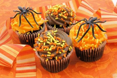 close up food: Halloween cupcake treats on orange patterned background