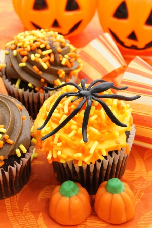Tasty Halloween cupcakes and candy on orange patterned background photo