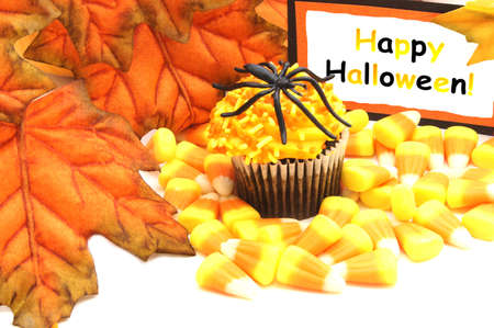 Happy Halloween tag with cupcake, candy and autumn leaves photo