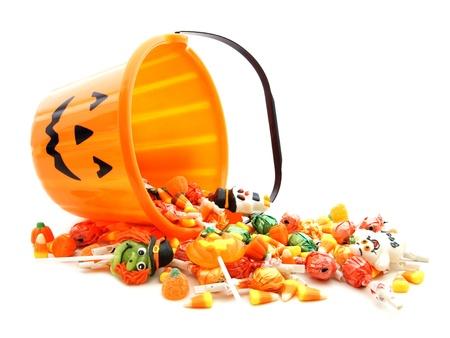 truc: Halloween jack-o-lantern emmer met morsen snoep over wit Stockfoto