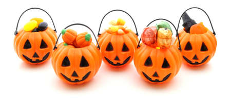 Five jack-o-lantern candy holders filled with a variety of candy photo