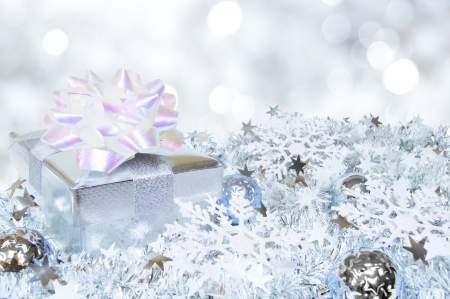 Silver Christmas scene with gift box, baubles and abstract light background photo