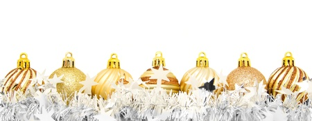 Gold Christmas baubles with garland arranged in a row over white photo