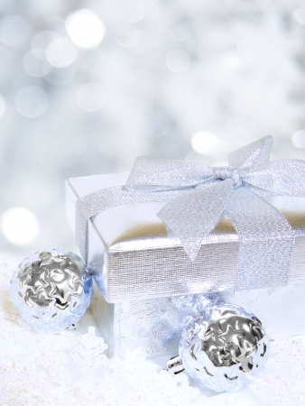 group of christmas baubles: Silver Christmas gift box with baubles and abstract light background Stock Photo