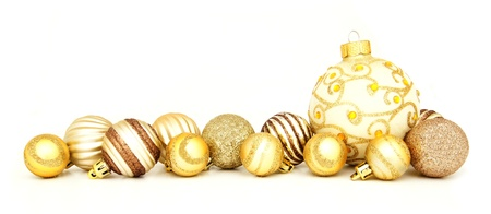 Group of gold Christmas baubles arranged as a border over white photo