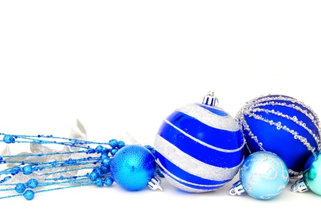 Group of blue Christmas baubles and branches arranged as a border over white photo