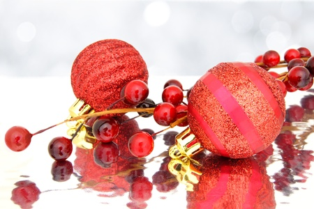 Red Christmas baubles and berry branch with twinkling light background photo