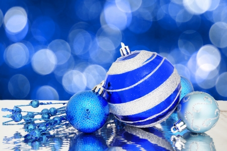 Blue Christmas baubles and berry branch with twinkling light background