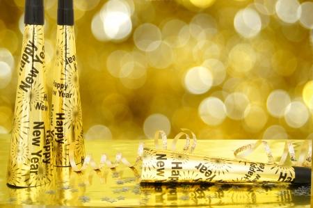 New Years Eve lawaaimakers en confetti met fonkelende gouden lichte achtergrond