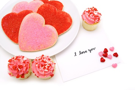 Handwritten I Love You card with heart shaped cookies and cupcakes photo