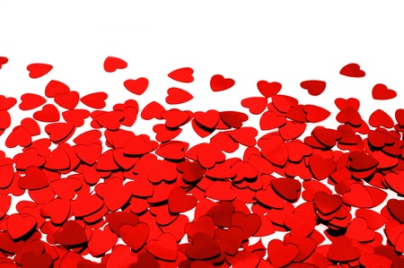 Red heart shaped confetti background or horizontal border over white photo