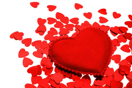 Red heart shaped confetti with single cloth heart over white photo