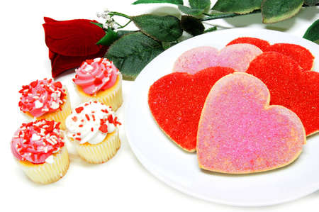shaped: Heart shaped Valentines Day cookies and cupcakes with rose over white Stock Photo