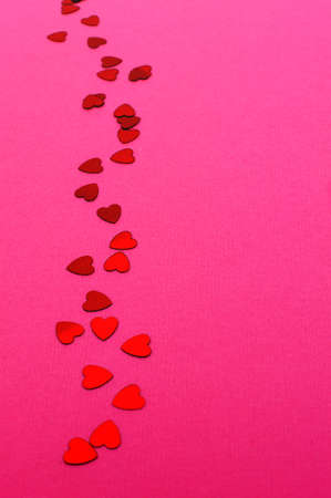 shaped: Trail of red heart shaped confetti on vertical pink paper background Stock Photo
