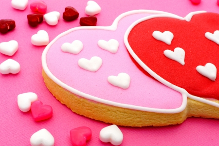 Heart shaped Valentines Day cookies and candies on pink paper background photo