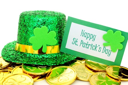 Happy St Patricks Day tag with party hat and gold coins over white photo