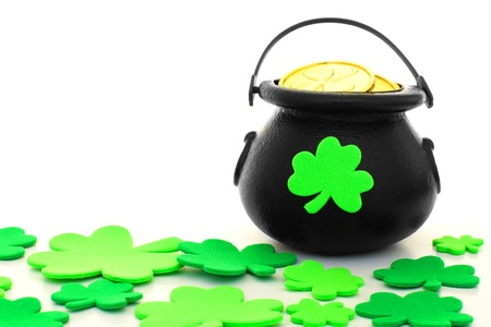 St Patricks Day pot of gold with scattered shamrocks over white photo