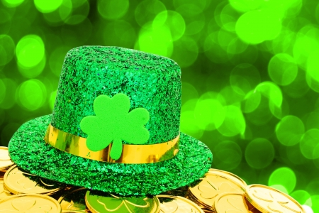 st  patricks: Shiny St Patricks Day hat and gold coins on green twinkling background Stock Photo