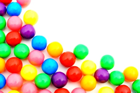 gumballs: Corner border of colorful gumball candies over white