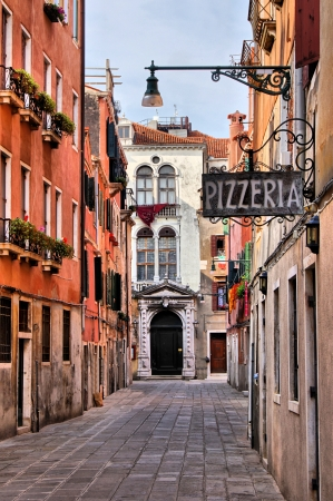 Quaint street in historic Venice, Italy with Pizzeria sign