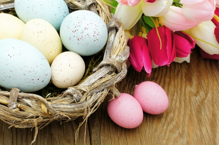 easter nest: Springtime Easter nest with eggs and flowers over a wood background