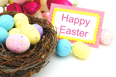 Happy Easter tag, springtime nest with eggs and flowers over white photo