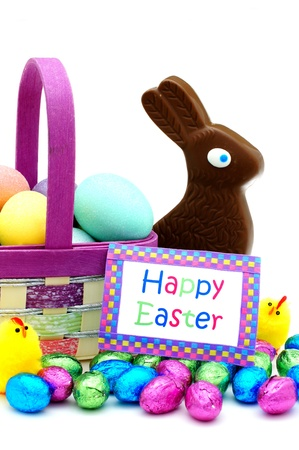 Easter basket close up with colorful eggs, chicks, candy and Happy Easter card over white Stock Photo - 18020019
