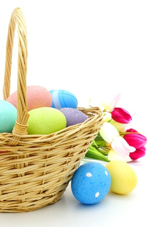 blue green background: Easter basket close up with colorful eggs and flowers over white