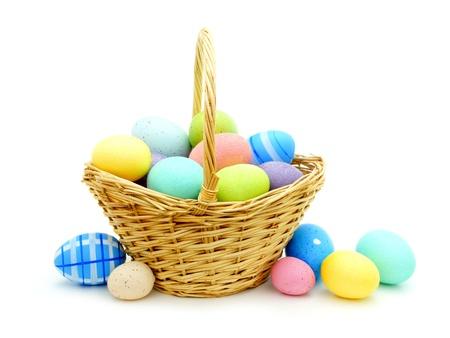 mimbre: Cesta de Pascua con los huevos coloridos sobre blanco Foto de archivo