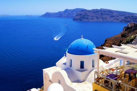 santorini greece: Blue dome church with boat, Oia village, Greece