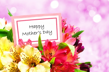 Happy Mothers Day tag among a bouquet of flowers with twinkling background