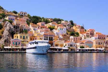 rhodes: Colorful houses lining the harbor at Symi, Greece Stock Photo