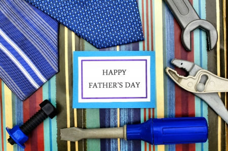 Happy Father Day tag with ties, and toy tools over patterned background