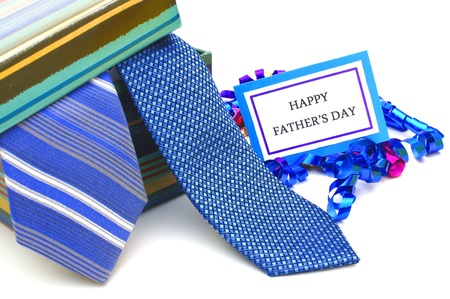 Happy Fathers Day tag with gift box and ties over white photo