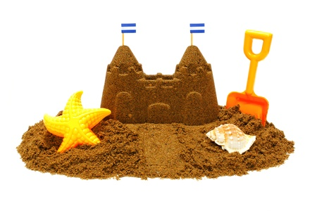 Sand castle with childs beach toys isolated on white 版權商用圖片