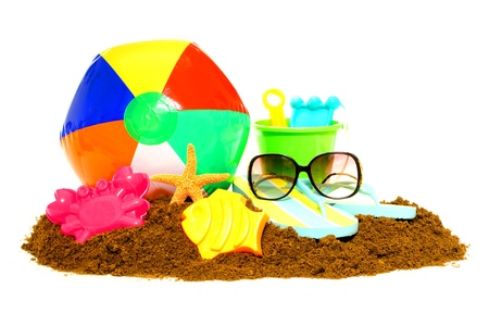Beach ball, toys, sunglasses and flip flops with sand isolated on white photo