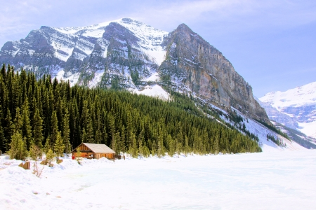 Log cabin along the shores of a frozen Lake Louise, Banff, Canada