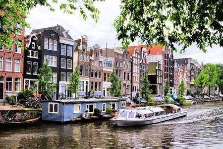 Boat traveling along the picturesque canals of Amsterdam, Netherlands